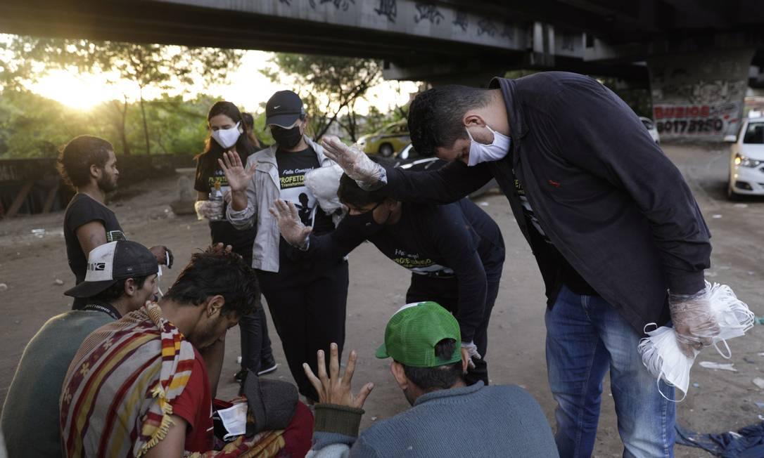 Os homens recebem orações de membros do projeto social Fala Comigo!, que também ofereceu ofereceu máscaras e alimentos em uma área conhecida como Cracolândia, durante o surto de coronavírus no Rio de Janeiro Foto: RICARDO MORAES / REUTERS