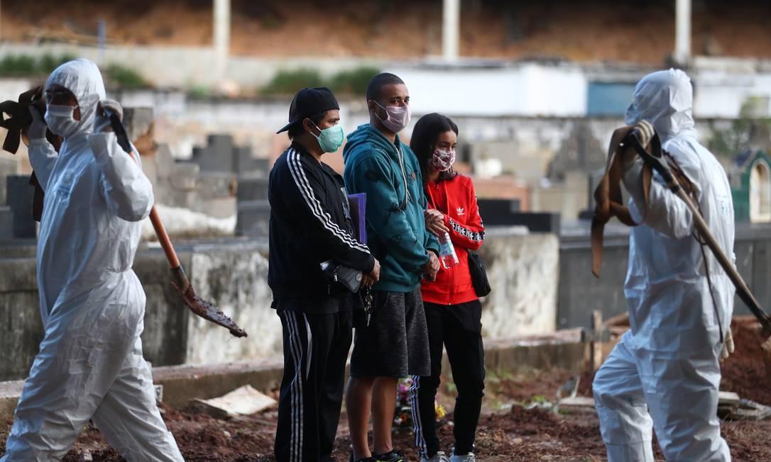 Parentes de uma idosa que morreu pela COVID-19 acompanham enterro em um cemitério no Rio de Janeiro Foto: PILAR OLIVARES / REUTERS