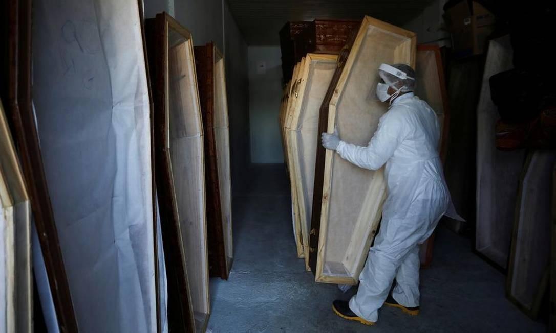 Funcionário de um serviço funerário de Manaus prepara caixões em meio ao surto de coronavírus Foto: Bruno Kelly / REUTERS