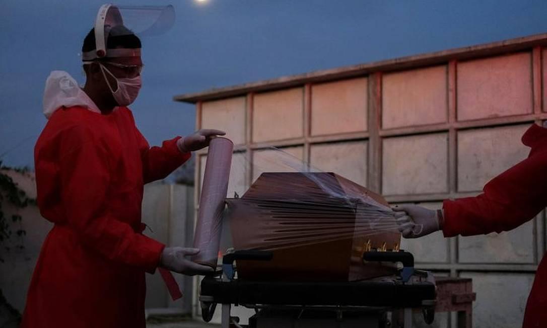 Coveiros preparam o caixão de homem que morreu com suspeita de Covid-19 no cemitério público de Duque de Caxias, no Rio de Janeiro Foto: Ricardo Moraes / REUTERS