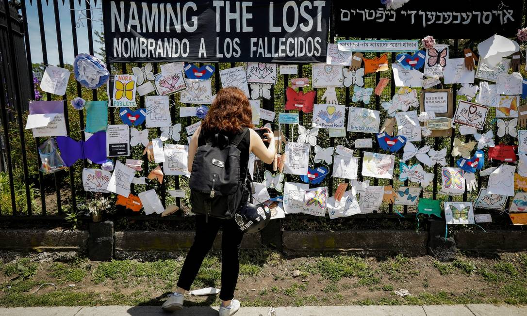 Mulher fotografa memorial em homenagem aos mortos pela Covid-19, diante do cemitério The Green-Wood, no Brooklyn, Nova York Foto: BRENDAN MCDERMID / REUTERS