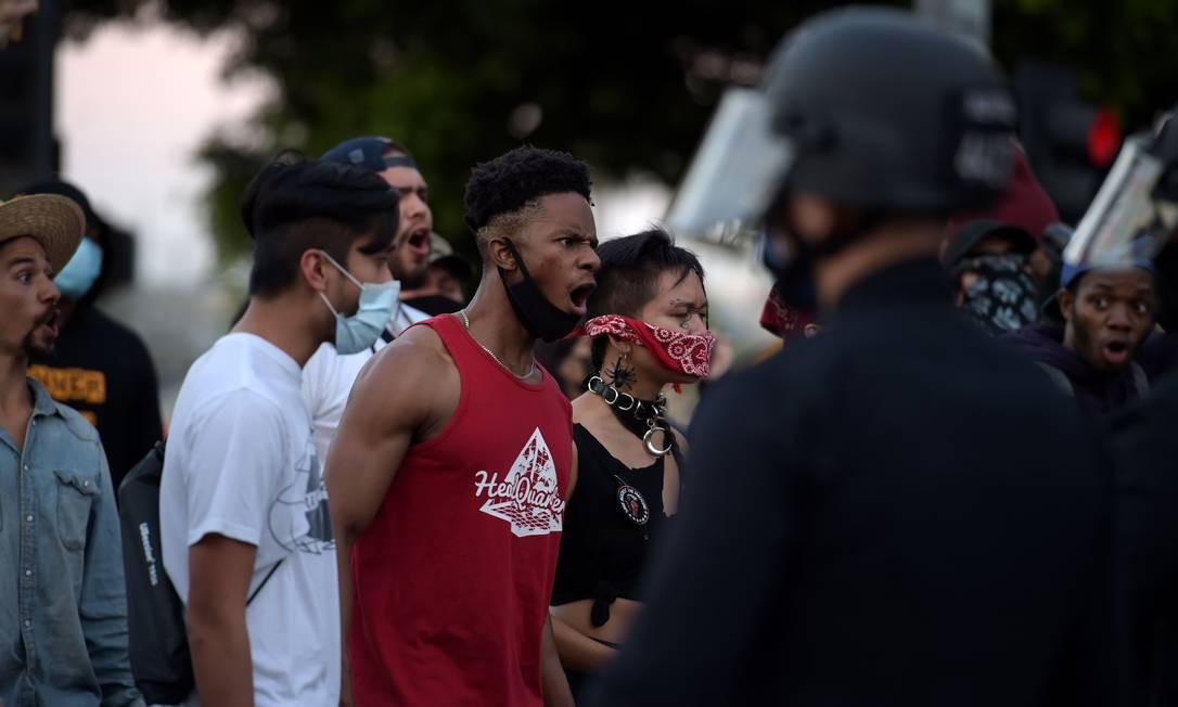 Manifestantes reagem na frente da polícia quando se reúnem no centro de Los Angeles, Califórnia. A barbárie da polícia de Minessota uniu minorias dos EUA em protestos na quarta-feira Foto: AGUSTIN PAULLIER / AFP