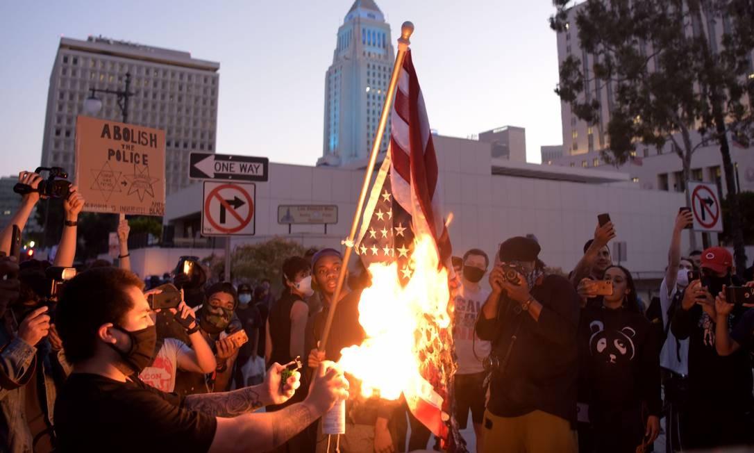 Manifestantes queimam bandeira dos Estados Unidos de cabeça para baixo no centro de Los Angeles, Califórnia Foto: AGUSTIN PAULLIER / AFP