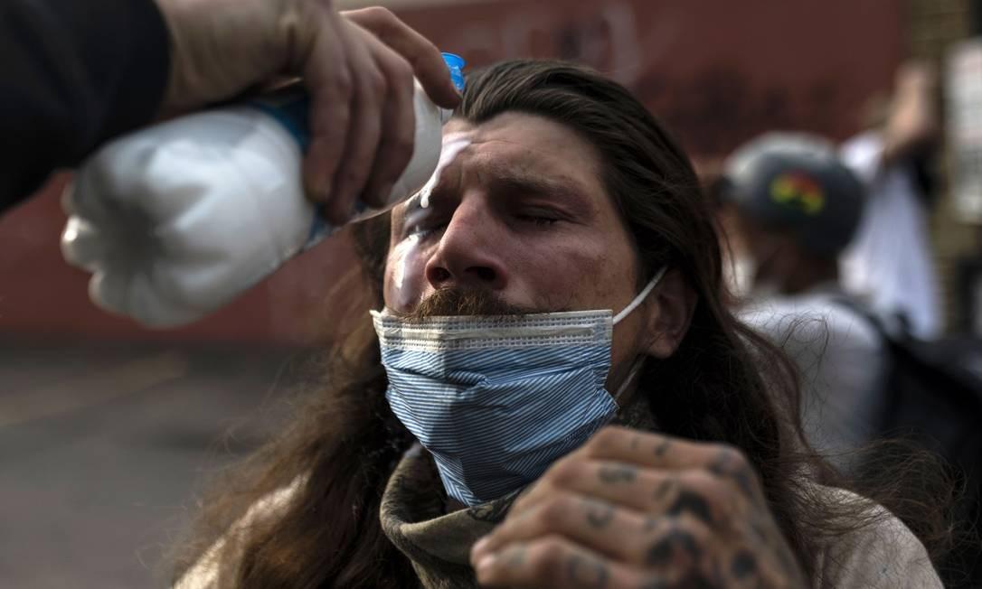 Manifestante lava rosto depois de ser atingido por spray de pimenta da polícia em Mineápolis, Minessota, onde o aconteceu a barbárie Foto: Stephen Maturen / AFP