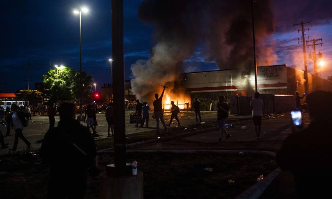 Manifestantes ateiam fogo em uma loja da Auto Zone, em Mineápolis Foto: Stephen Maturen / AFP