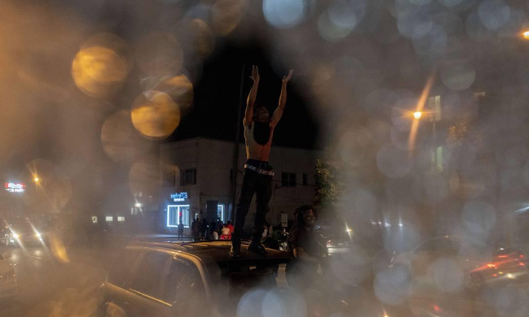 Manifestante é visto, através de vidro quebrado da janela de um ônibus, em cima de carro estacionado Foto: Stephen Maturen / AFP