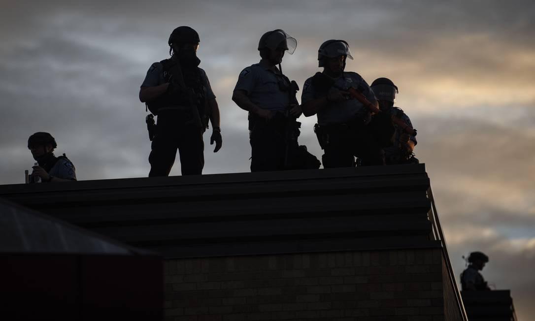 Policiais observam manifestação do alto de um terraço, em Mineápolis Foto: Stephen Maturen / AFP