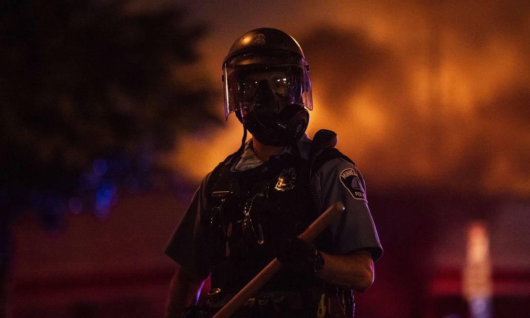 Policial empunha cacetete em meio a protestos na noite de quarta-feira, quando população revoltada com a morte de George Floyd chegou a atear fogo e saquear lojas em Mineápolis Foto: Stephen Maturen / AFP