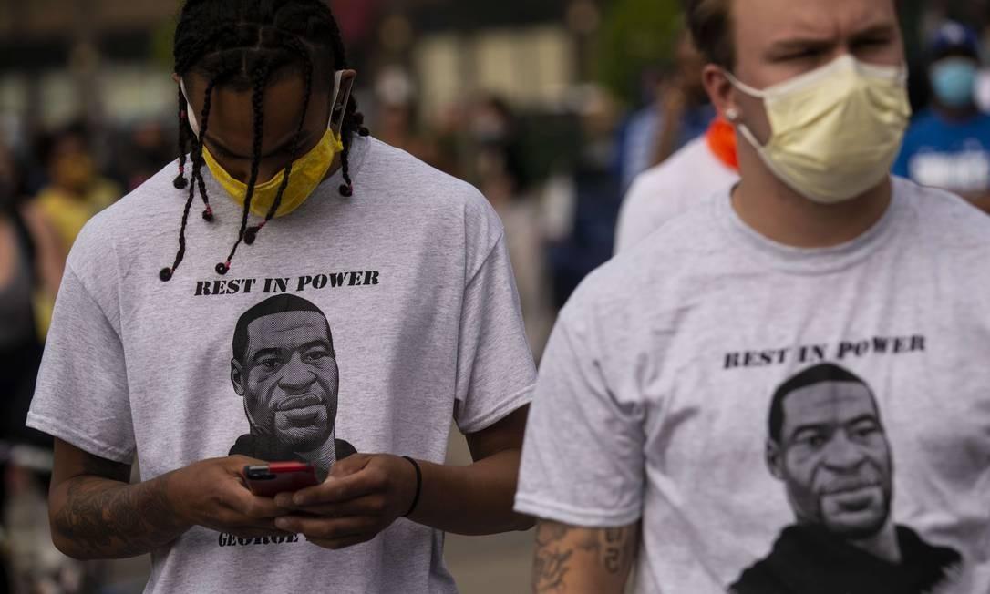 """""""Descance no poder"""", um trocadilho com a sigla em inglês RIP (""""rest in peace"""", descanse em paz), em referência ao luto pela morte de George Floyd e ao orgulho negro, é o que diz a mensagem estampada na camisa de dois manifestantes em Mineápolis Foto: Stephen Maturen / AFP"""