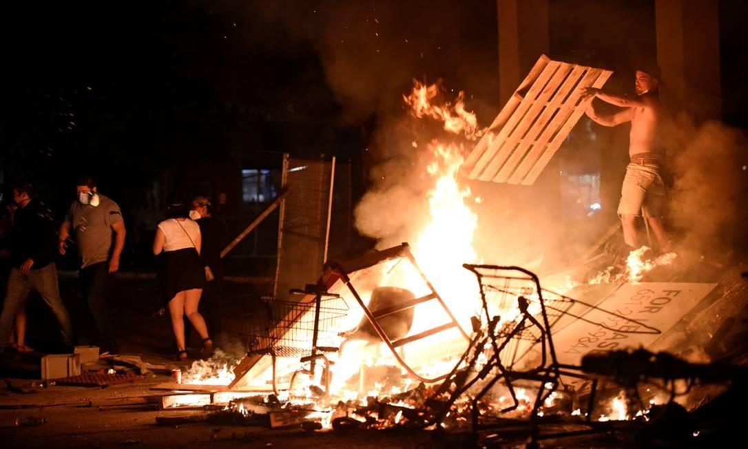 Manifestantes incendeiam barricada com objetos de madeira na 26ª Avenida, próximo ao departamento de polícia onde estão lotados os policiais que mataram George Floyd, em Mineápolis, Minessota, EUA. Os protestos aconteceram durante toda a quarta-feira e ficou mais violento durante a noite Foto: NICHOLAS PFOSI / REUTERS