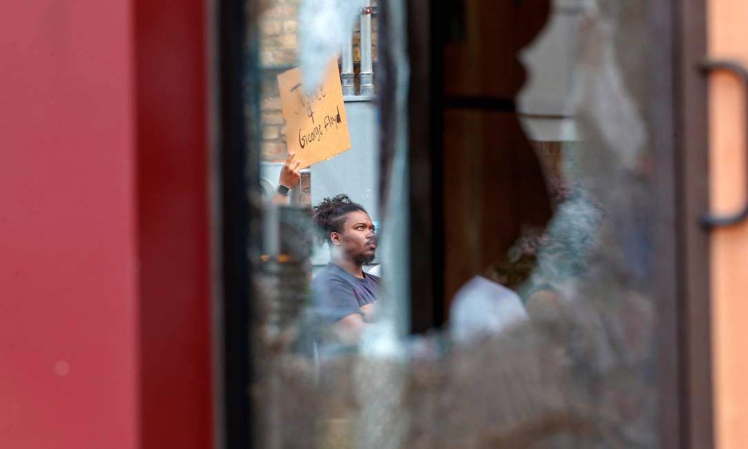 Manifestante fotografado através da porta da frente destruída da delegacia da Terceira Delegacia de Minneápolis Foto: ERIC MILLER / REUTERS