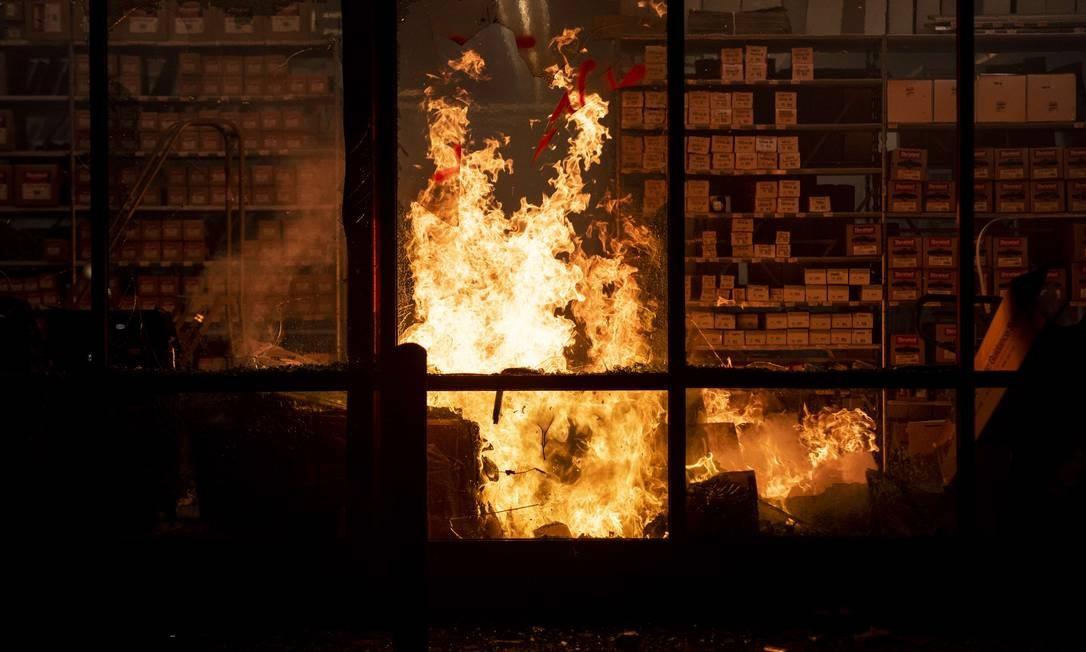 Depois de longo confrontos com a polícia, durante a quarta-feira, imóveis no entorno do 3º Distrido de Polícia foram alvos da revolta de quem protestava em Mineápolis Foto: Stephen Maturen / AFP