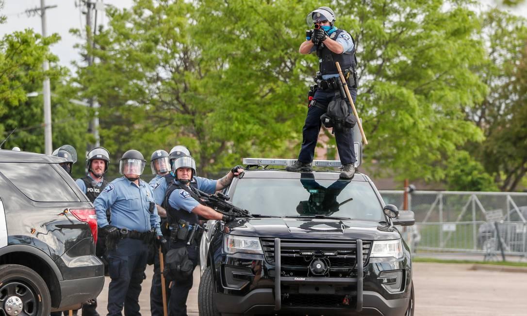Policial, de cima do teto de carro oficial, mira em manifestantes em Mineápolis Foto: ERIC MILLER / REUTERS
