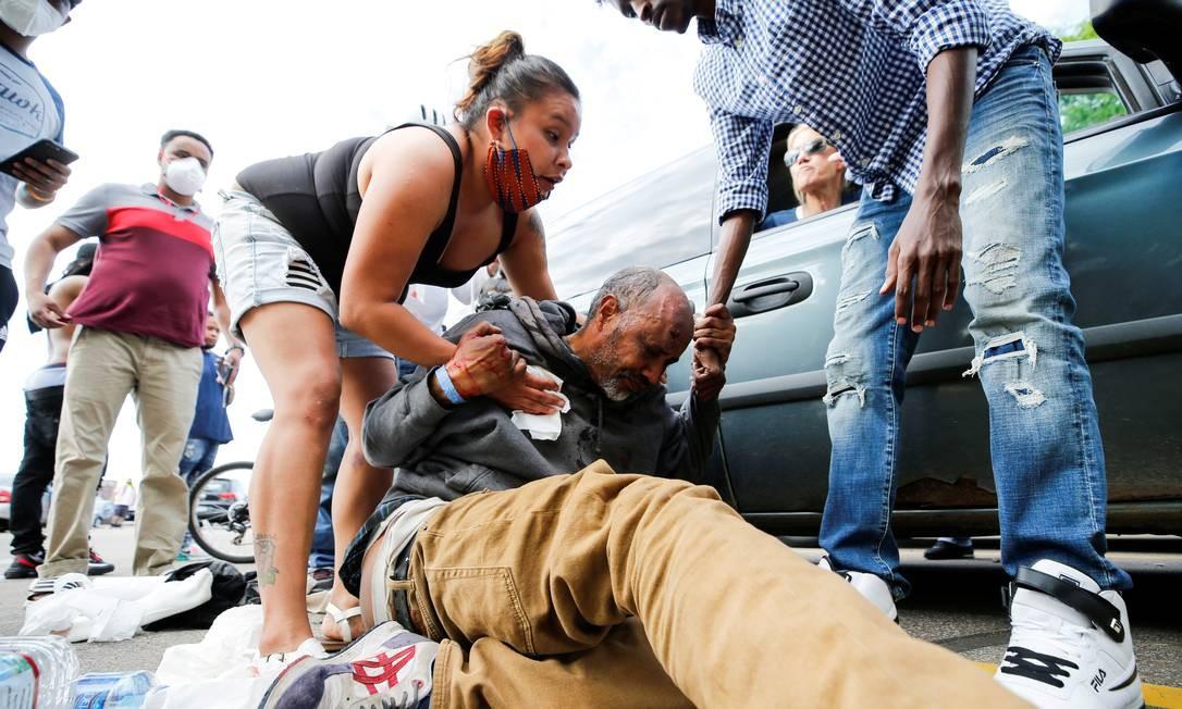 Manifestante atingido na cabeça é socorrido durante protestos na quarta-feira, que atravessaram a madrugada Foto: ERIC MILLER / REUTERS