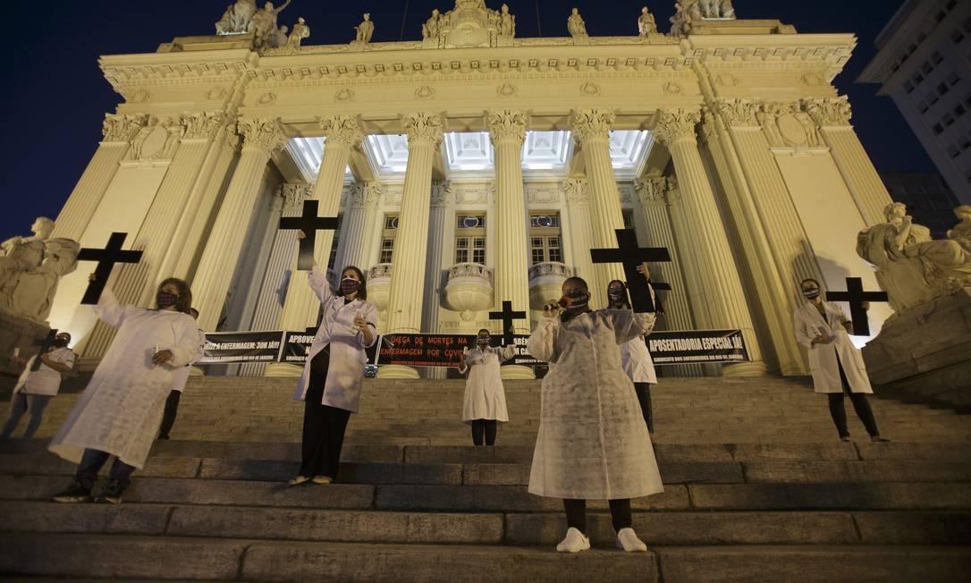Profissionais de saúde seguram cruzes em referência a colegas mortos, durante um ato em frente à Alerj, no Dia Internacional da Enfermagem em 2020 Foto: Alexandre Cassiano / Agência O Globo - 12/05/2020