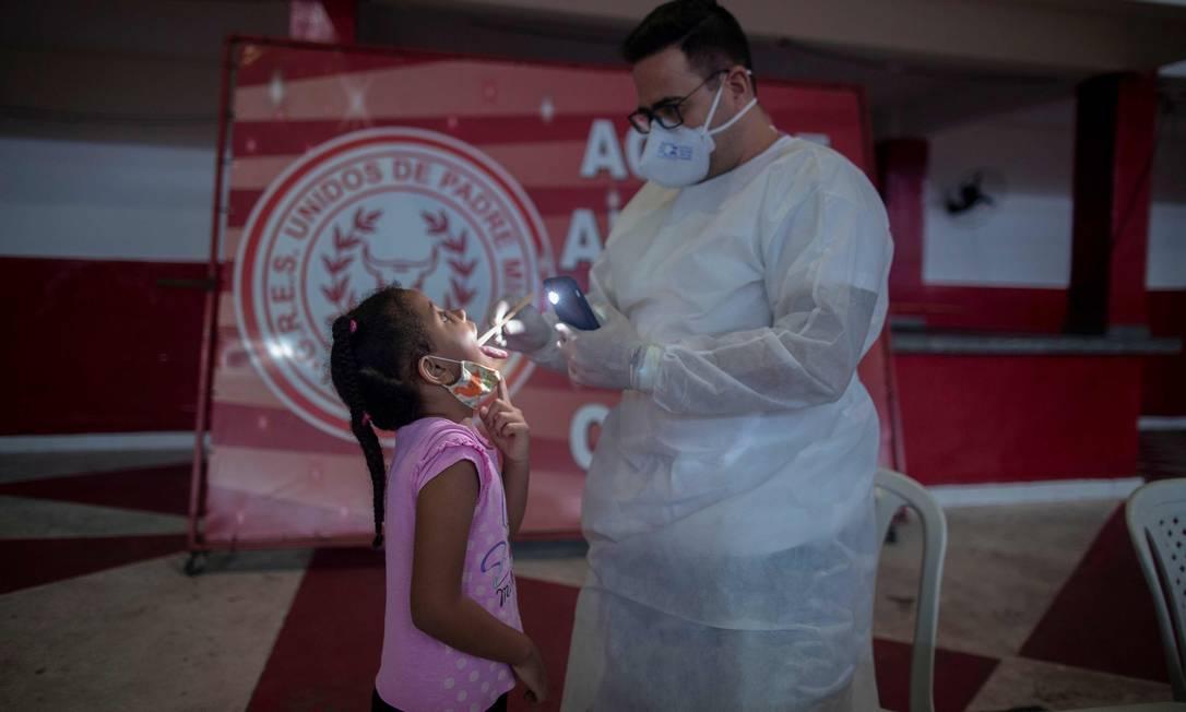 Um médico atende uma menina com sintomas do novo coronavírus durante um dia de exames de saúde gratuitos na sede da escola de samba Unidos de Padre Miguel Foto: MAURO PIMENTEL / AFP - 24/05/2020