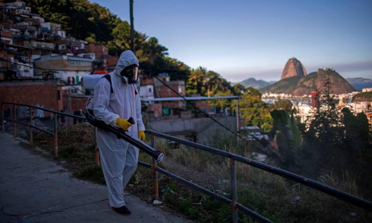 Voluntário desinfeta uma via na favela Santa Marta, no Rio de Janeiro Foto: MAURO PIMENTEL / AFP - 20/04/2020
