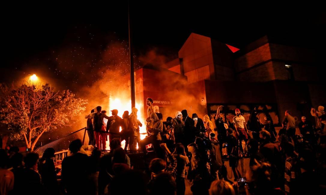 Manifestantes se reúnem depois de atear fogo na entrada de uma delegacia em Minneapolis Foto: CARLOS BARRIA / REUTERS