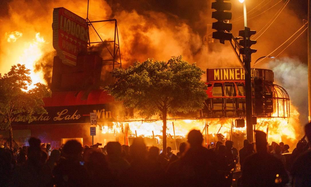 Loja de bebidas em chamas perto da delegacia, em Minneapolis, Minnesota Foto: KEREM YUCEL / AFP