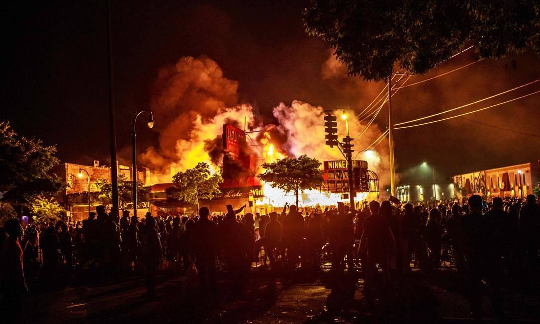 Multidão cerca loja de bebidas incendiada em Minneapolis Foto: KEREM YUCEL / AFP