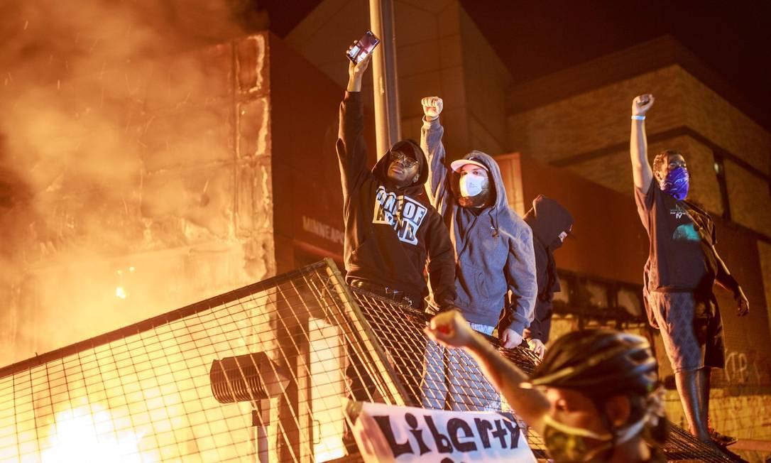 Manifestantes erguem punho cerrado as chamas se espalham pela frente da Terceira Delegacia de Polícia, na noite de quinta-feira Foto: KEREM YUCEL / AFP