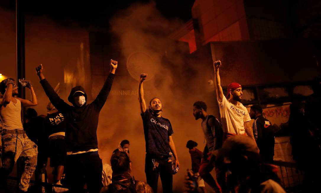 Depois de atearem fogo na entrada da delegacia em Minneapolis, manifestantes erguem o punho cerrado – gesto ficou conhecido como símbolo da luta racial através dos Panteras Negras, na conquista de direitos civis Foto: CARLOS BARRIA / REUTERS