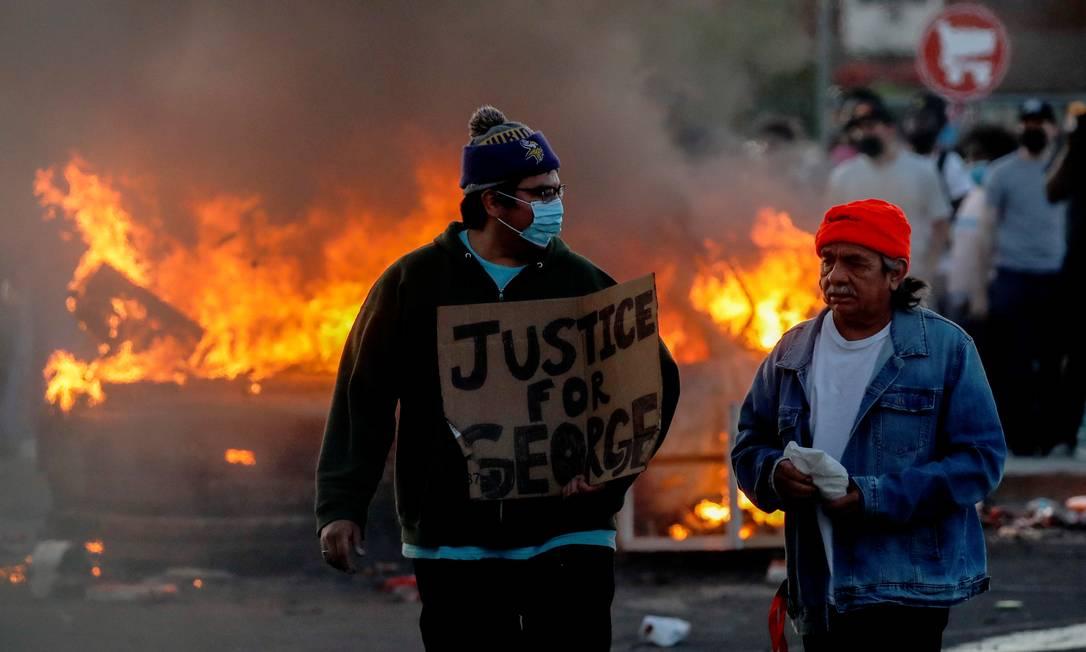 Usando máscara de proteção, homem carrega cartaz que pede justiça; ao fundo, uma barricada em chamas Foto: Carlos Barria / REUTERS