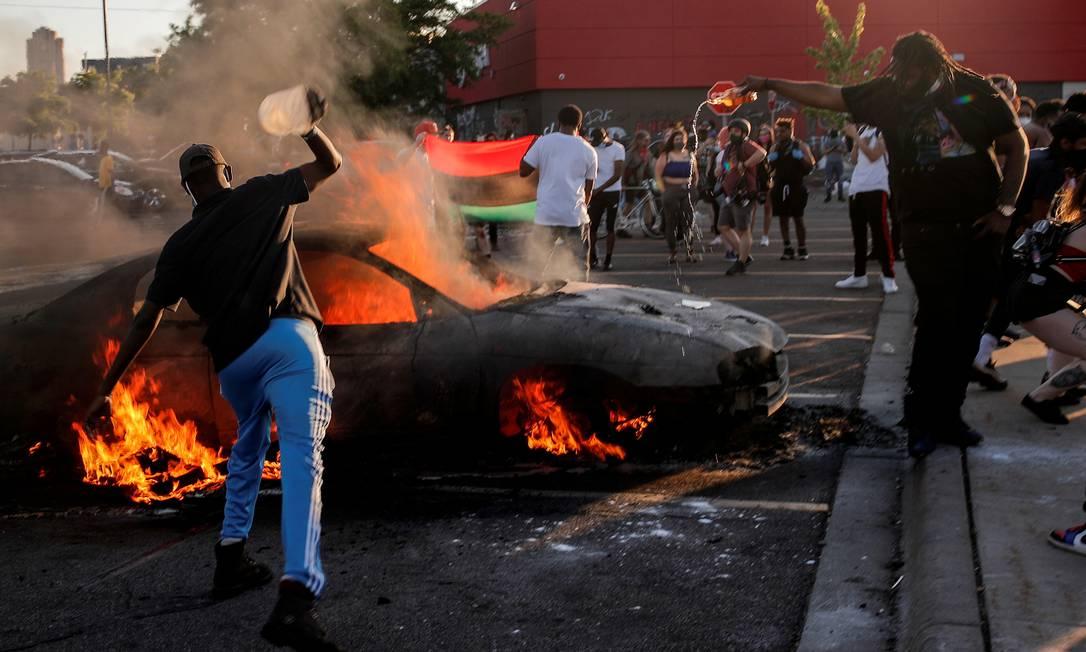 Manifestantes ateiam fogo em veículo em Minneapolis Foto: Carlos Barria / REUTERS