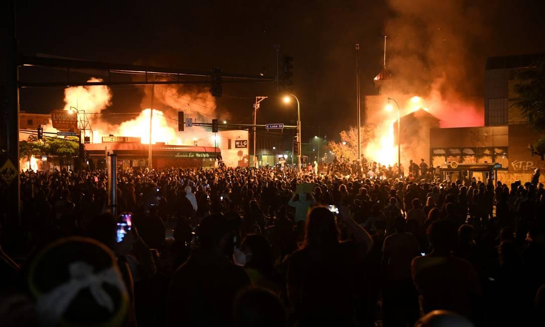 Milhares de pessoas protestam contra o assassinato de George Floyd em Minneapólis; ao fundo, claridade mostra imóveis incendiados Foto: NICHOLAS PFOSI / REUTERS