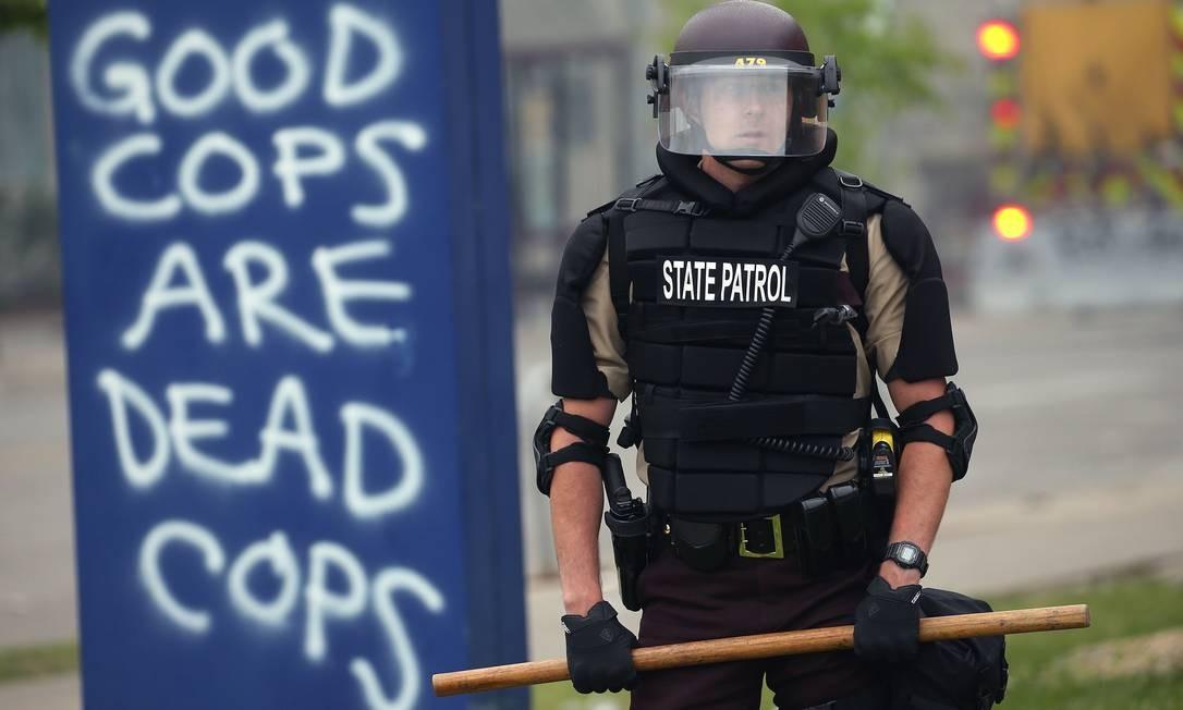 """Agente da Guarda Nacional, com cacetete empunhado, aparece ao lado de pichaão que diz: """"policial bom é policial morto"""" Foto: SCOTT OLSON / AFP"""