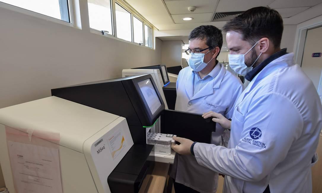 Funcionários introduzem amostras dentro de sequenciador. Resultado em 72 horas Foto: NELSON ALMEIDA / AFP