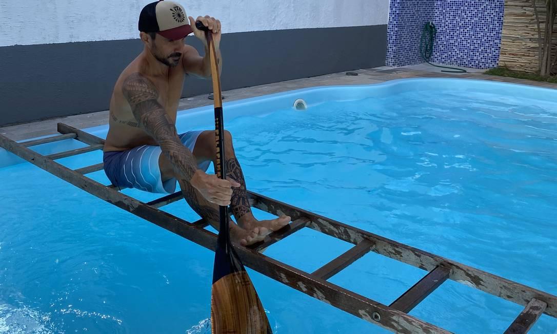 Professor do clube de canoa havaiana Itaipu Surf Hoe, Fábio Valongo adaptou uma escada na piscina de casa para simular a remada Foto: Divulgação/Paula March