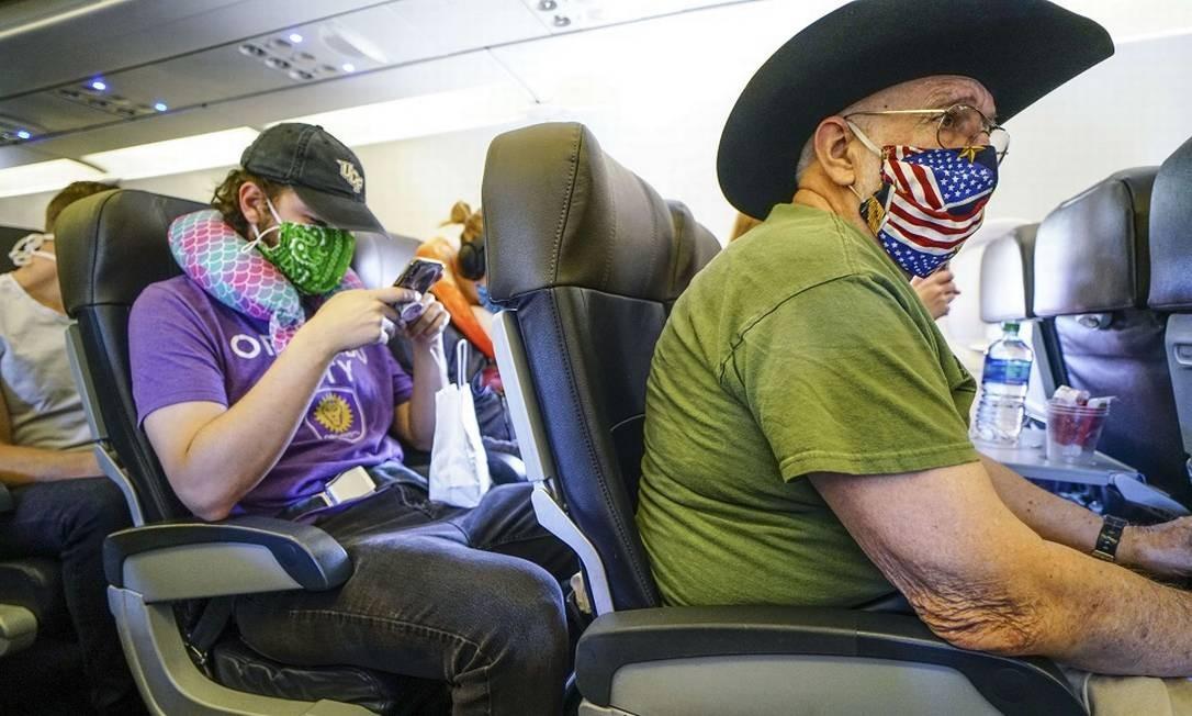Passageiros usam máscaras a bordo de um voo da American Airlines entre San Diego e Charlotte Foto: Sandy Huffaker / AFP