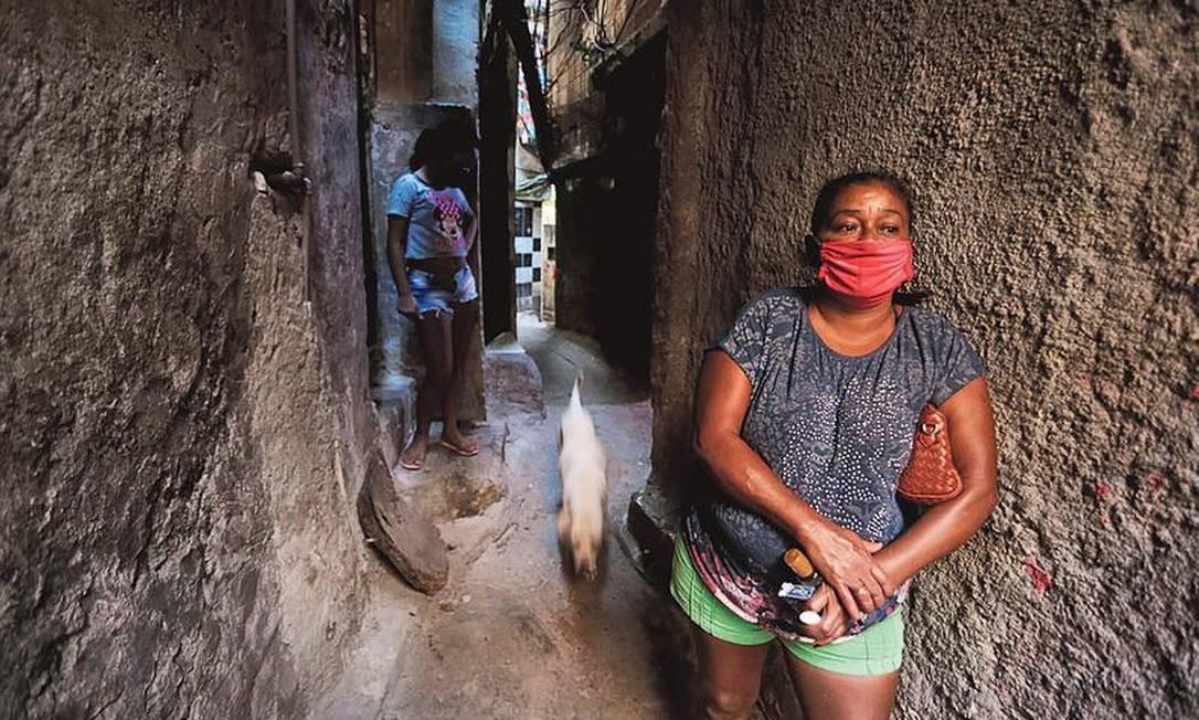 Moradora da Rocinha, onde já houve 55 óbitos, usa máscara em viela: dificuldade para manter distância Foto: Domingos Peixoto / Agência O GLOBO