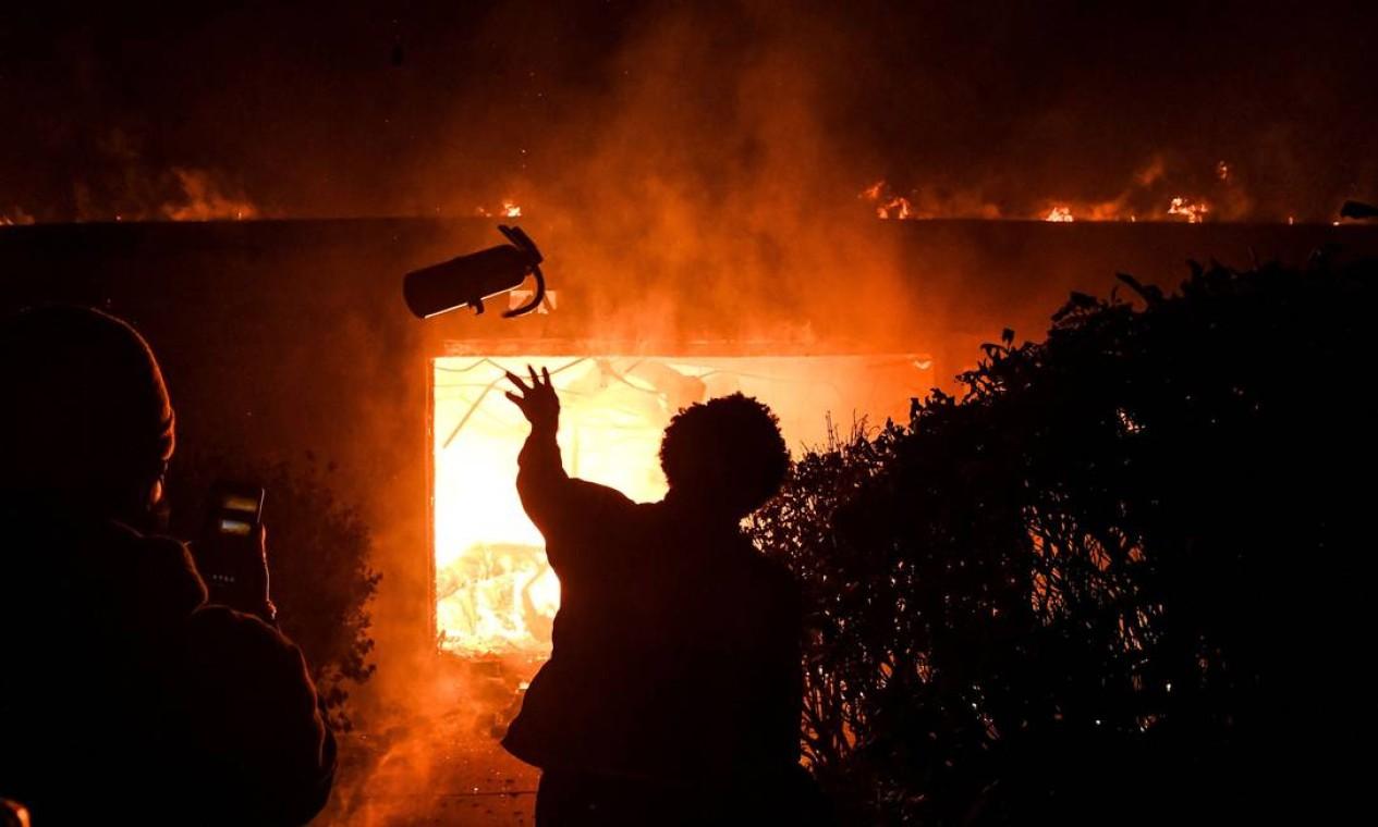 Manifestante arremessa extintor em imóvel em chamas, na quarta noite de protestos pelo assassinato de George Floyd, que foi acusado de ter comprado com uma nota falsa de 20 dólares em loja de conveniência de Minneapolis Foto: CHANDAN KHANNA / AFP