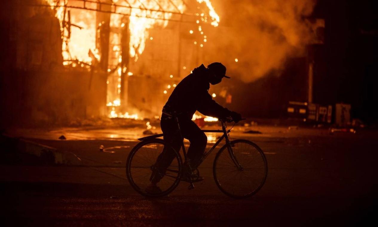 Homem passa de bicicleta em frente a posto de gasolina incendiado Foto: Stephen Maturen / AFP