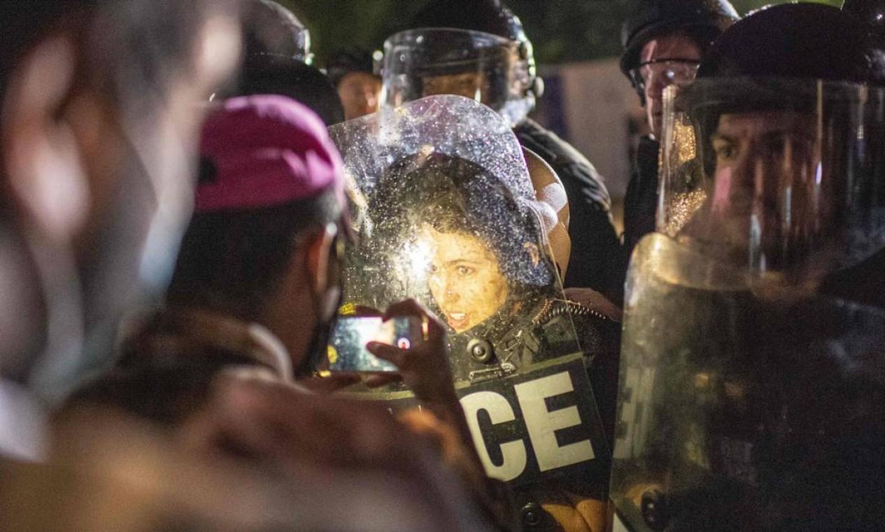 Manifestante encara agentes da polícia de choque de Minnesota Foto: ERIC BARADAT / AFP