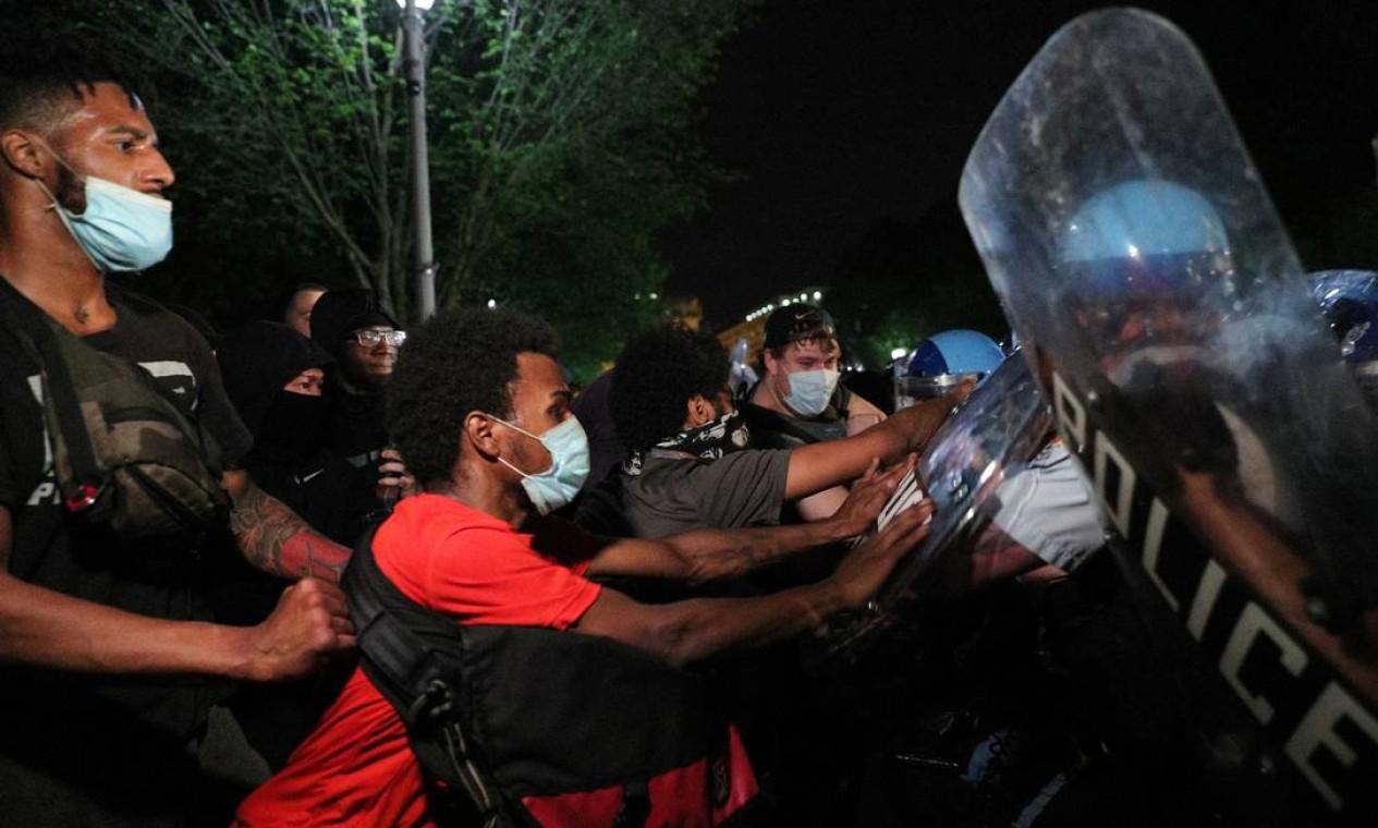 Manifestantes empurram tropa de choque da polícia na noite de sexta-feira Foto: TOM BRENNER / REUTERS
