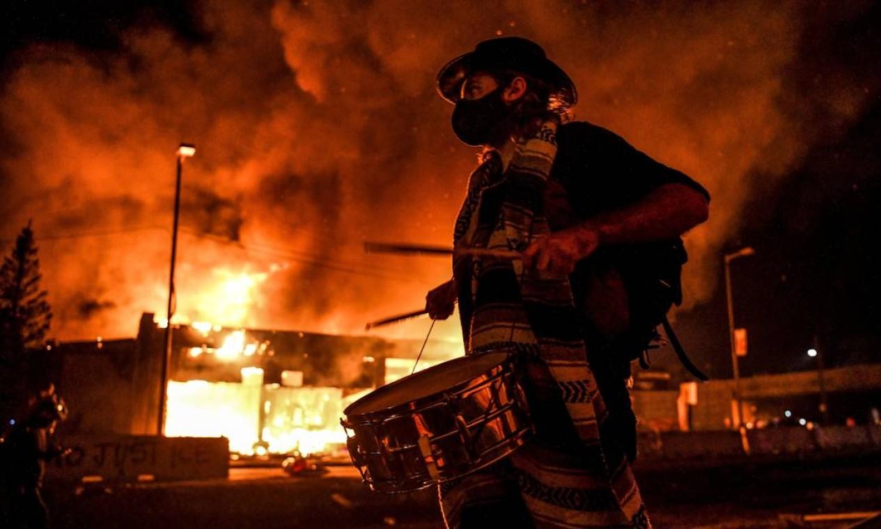 Manifestante, usando máscara de proteção, toca instrumento de percussão diante de incêndio causado por manifestantes, em Minneapolis Foto: CHANDAN KHANNA / AFP