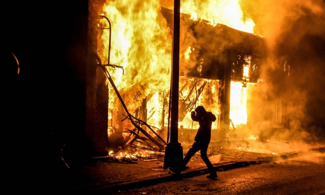 Homem atira pedra em edifícil em chamas em Minneapolis Foto: CHANDAN KHANNA / AFP