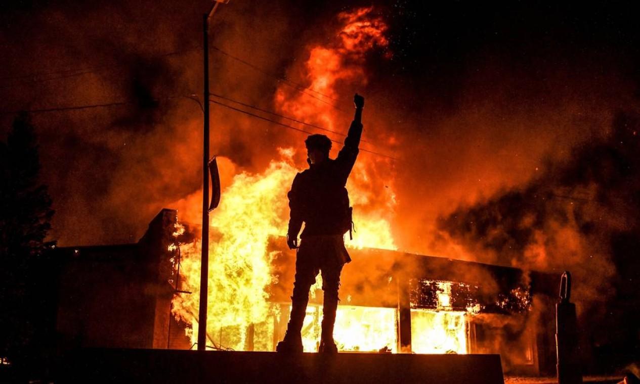Manifestante ergue punho cerrado diante de imóvel em chamas na cidade de Minneapolis, onde George Floyd foi assassinado por policiais do estado de Minnesota, nos EUA Foto: CHANDAN KHANNA / AFP