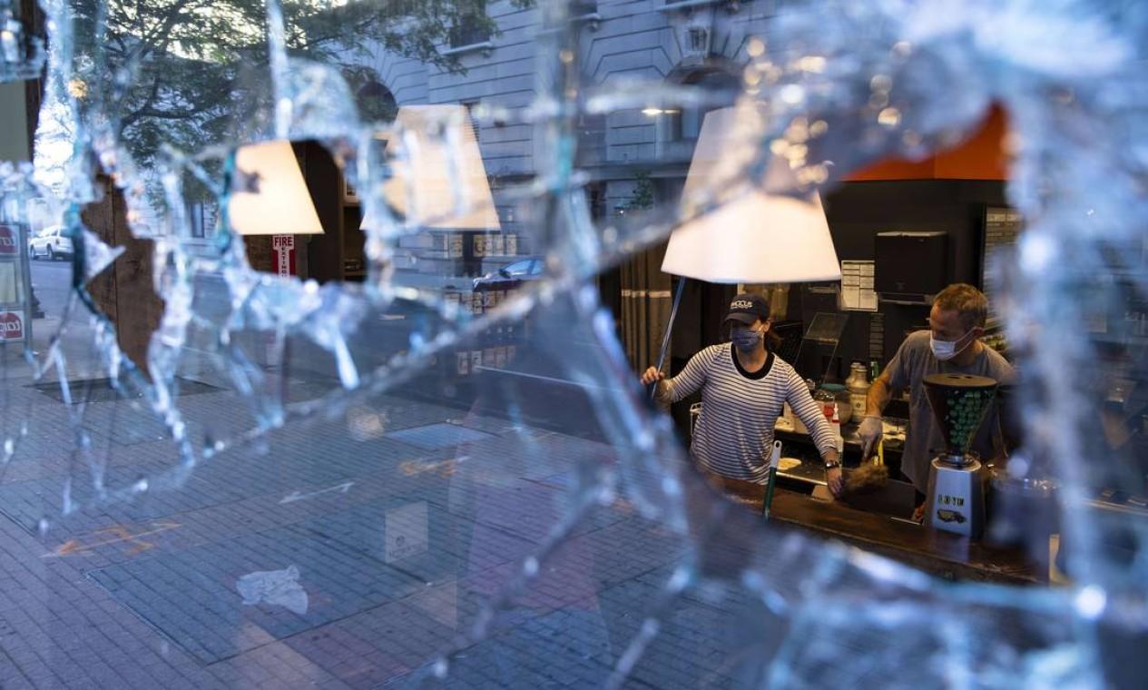 Trabalhadores limpam loja danificada por manifestantes em Louisville, Kentucky Foto: Brett Carlsen / AFP