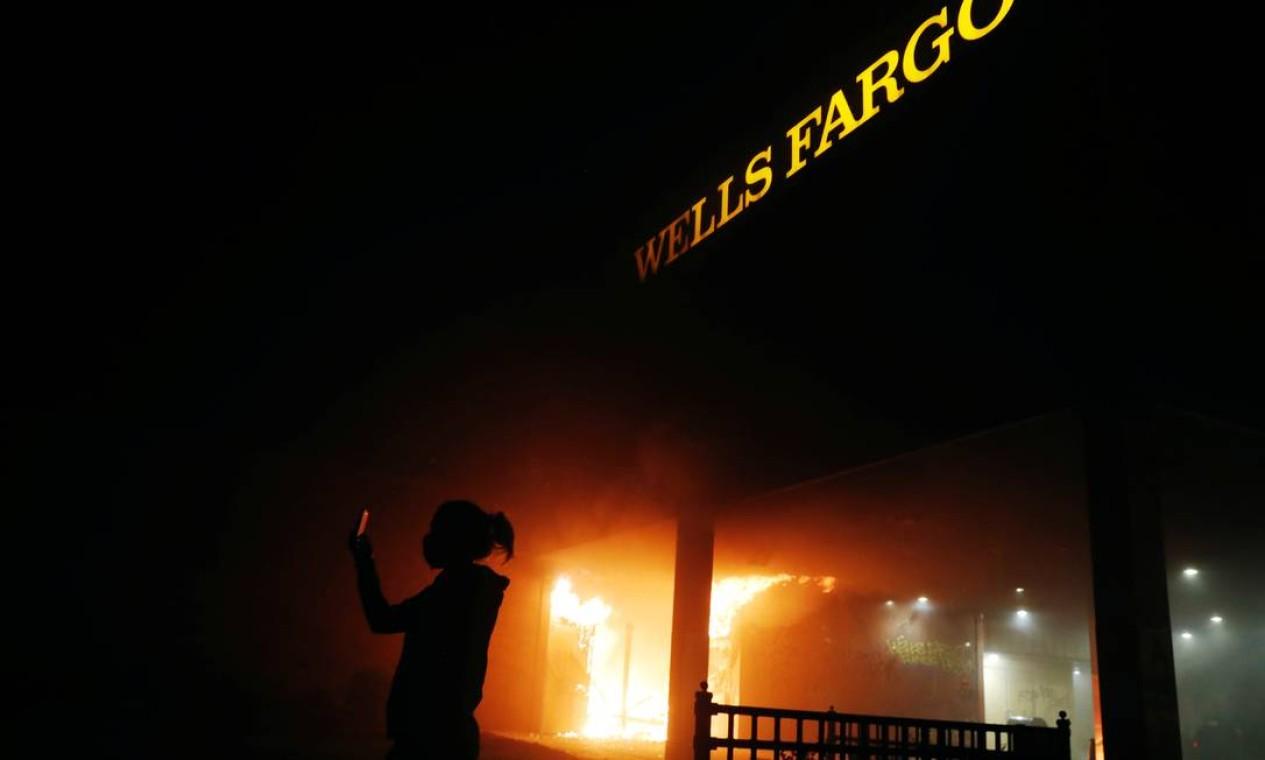 Manifestante faz selfie diante de agência do banco Wells Fargo, alvo de inúmeras ações sobre fraude financeira, em chamas Foto: LUCAS JACKSON / REUTERS