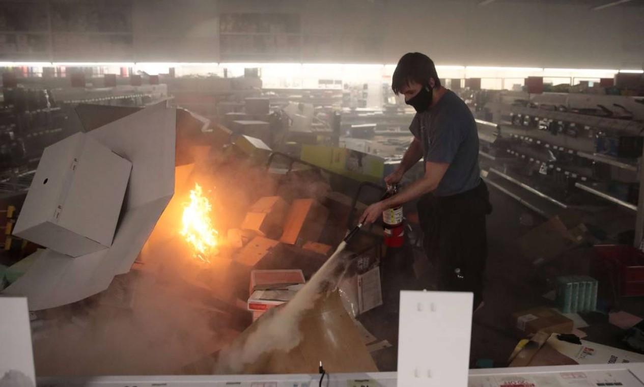 Trabalhador usa extintor para conter foco de incêndio dentro de loja revirada Foto: SCOTT OLSON / AFP