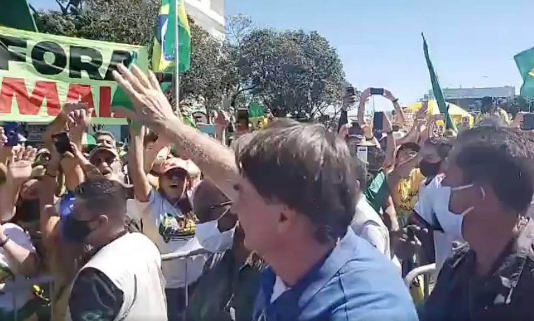 Sem máscara, Bolsonaro cumprimenta apoiadores em protesto em Brasília. Uma das faixas é de protesto contra o presidente da Câmara, Rodrigo Maia (DEM-RJ) Foto: Reprodução Facebook