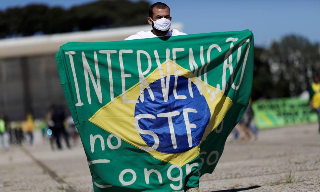 """Um apoiador do presidente Jair Bolsonaro segura uma bandeira com a frase """"Intervenção no Supremo Tribunal Federal e no Congresso Nacional"""" durante o protesto em Brasília Foto: UESLEI MARCELINO / REUTERS"""