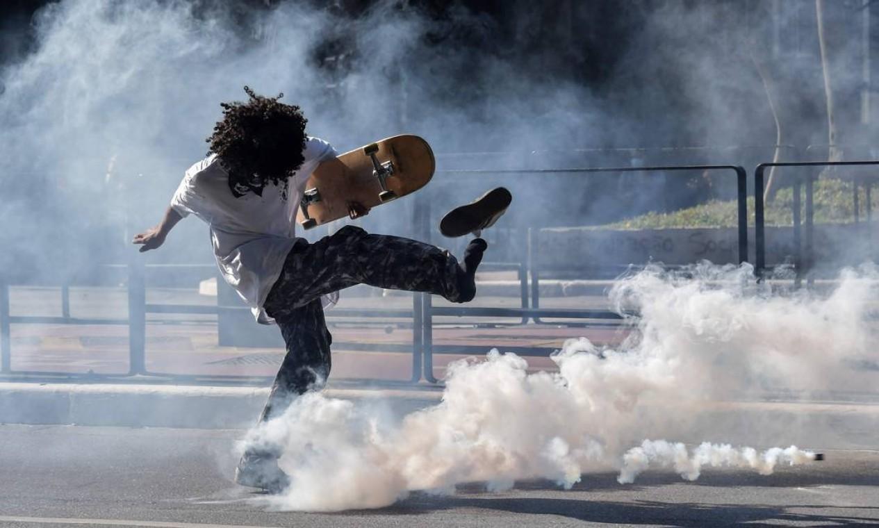 Manifestante antigoverno chuta um cartucho de gás lacrimogêneo lançado por policiais durante os confronto na Av. Paulista Foto: NELSON ALMEIDA / AFP