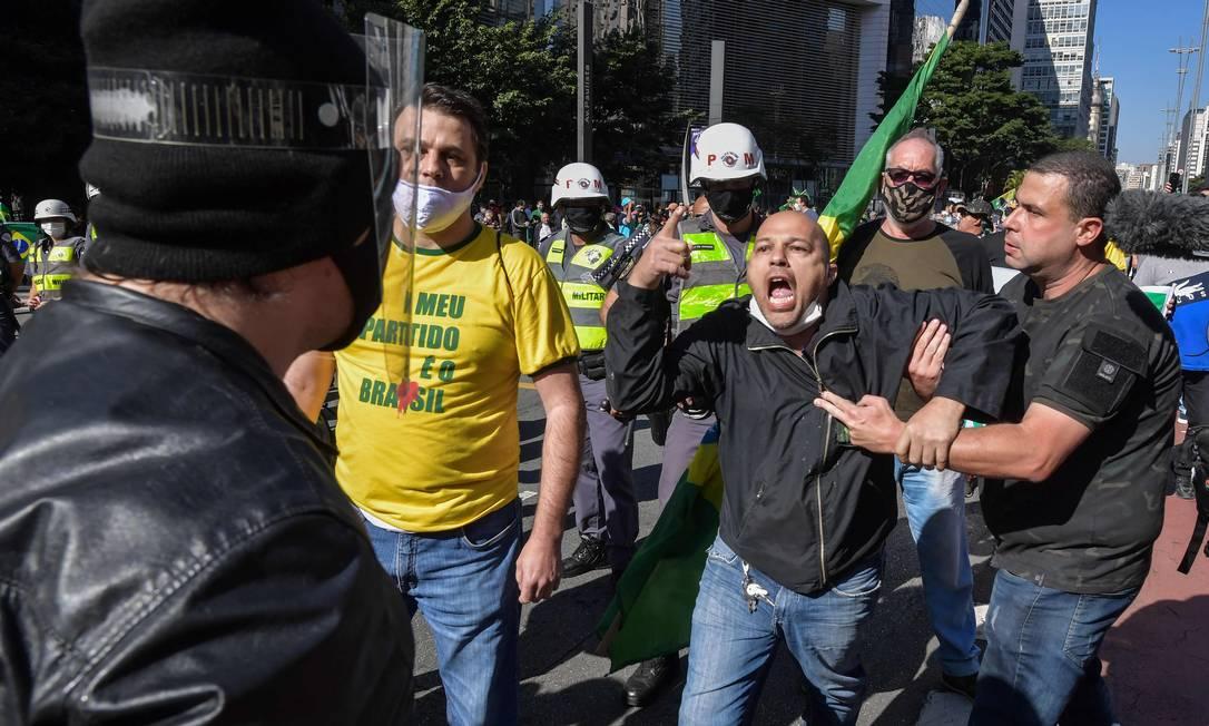 Um defensor do presidente Jair Bolsonaro discute com um torcedor antigoverno durante protesto na Avenida Paulista Foto: NELSON ALMEIDA / AFP