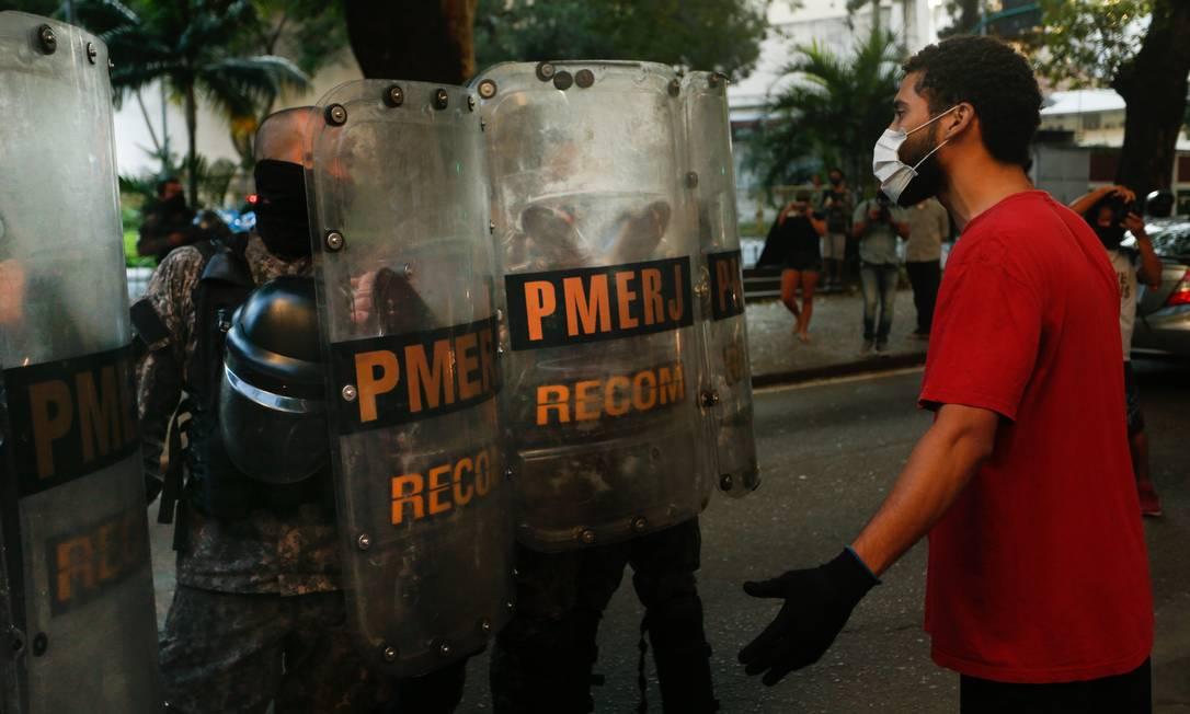 Manifestante discute com policiais durante ato na tarde deste domingo, em Laranjeiras Foto: ROBERTO MOREYRA / Agência O Globo