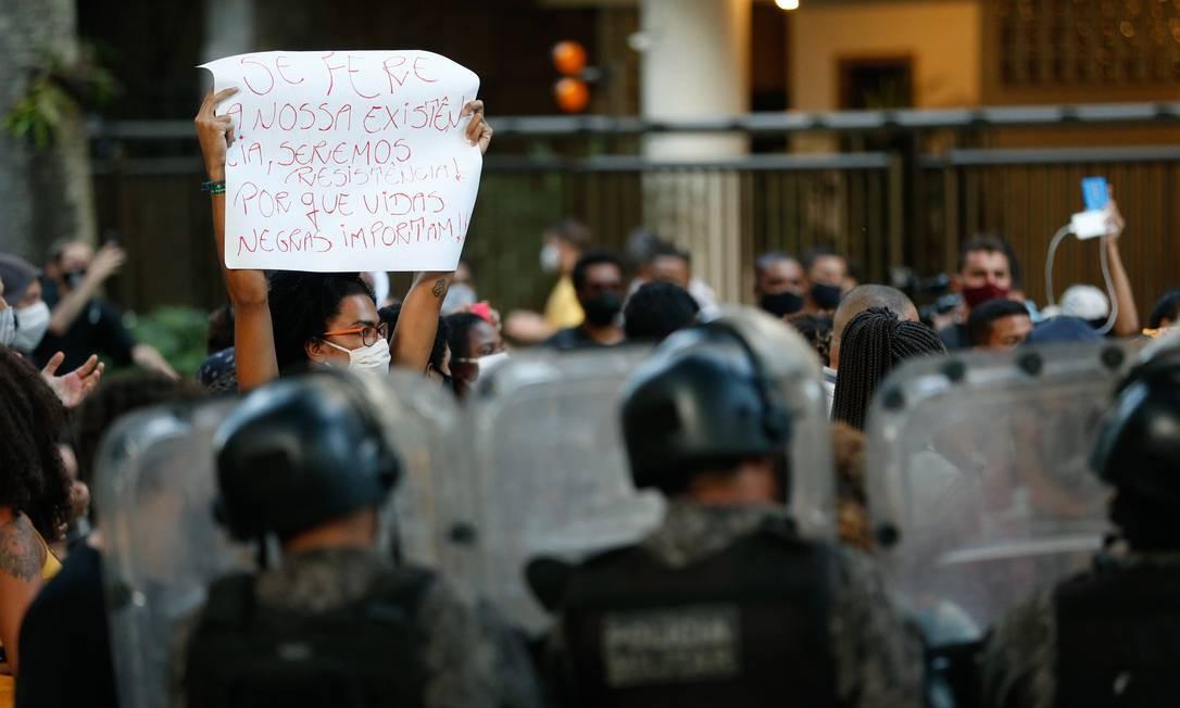 """Em meio a policiais, uma manifestante exibe cartaz com a mensagem """"Se fere nossa existância, seremos resistência porque vidas negras importam Foto: ROBERTO MOREYRA / Agência O Globo"""